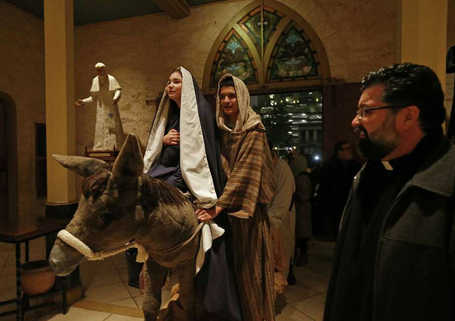 Angela Perez, 15, as Mary, (from left) Alessandro Santos, 14, as Joseph, and others are allowed in to San Fernando Cathedral by Father Victor Valdez (right) during the annual La Gran Posada held Sunday, Dec. 17, 2017. La Gran Posada which is organized by San Fernando Cathedral, tells the story of Mary and Joseph's journey to find a place to stay and for Jesus to be born, began at Milam Park and made its way through downtown with stops in Market Square, the Spanish Governor's Palace, City Hall, the Bexar County Courthouse and ended at San Fernando Cathedral, where Mary and Joseph were allowed in. Photo: Edward A. Ornelas, Staff / San Antonio Express-News / © 2017 San Antonio Express-News