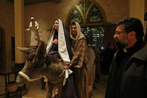 Angela Perez, 15, as Mary, (from left) Alessandro Santos, 14, as Joseph, and others are allowed in to San Fernando Cathedral by Father Victor Valdez (right) during the annual La Gran Posada held Sunday, Dec. 17, 2017. La Gran Posada which is organized by San Fernando Cathedral, tells the story of Mary and Joseph's journey to find a place to stay and for Jesus to be born, began at Milam Park and made its way through downtown with stops in Market Square, the Spanish Governor's Palace, City Hall, the Bexar County Courthouse and ended at San Fernando Cathedral, where Mary and Joseph were allowed in.