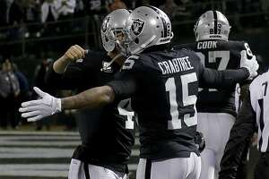 Oakland Raiders quarterback Derek Carr (4) and wide receiver Michael Crabtree (15) celebrate after connecting on a touchdown during the second half of an NFL football game against the Dallas Cowboys in Oakland, Calif., Sunday, Dec. 17, 2017. (AP Photo/Eric Risberg)