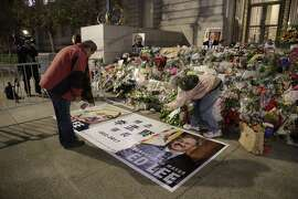 Jack Fong bows respect for Mayor Ed Lee's memorial and Donna Iverson take photos at the steps of City Hall on Sunday, Dec. 17, 2017 in San Francisco, CA.