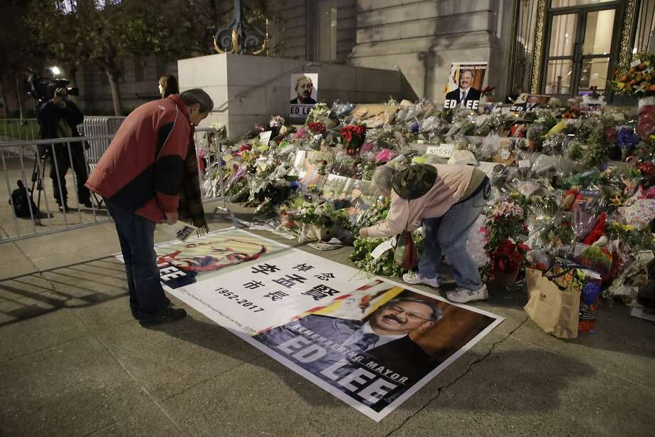 Jack Fong bows respect for Mayor Ed Lee's memorial and Donna Iverson take photos at the steps of City Hall on Sunday, Dec. 17, 2017 in San Francisco, CA. Photo: Paul Kuroda, Special To The Chronicle