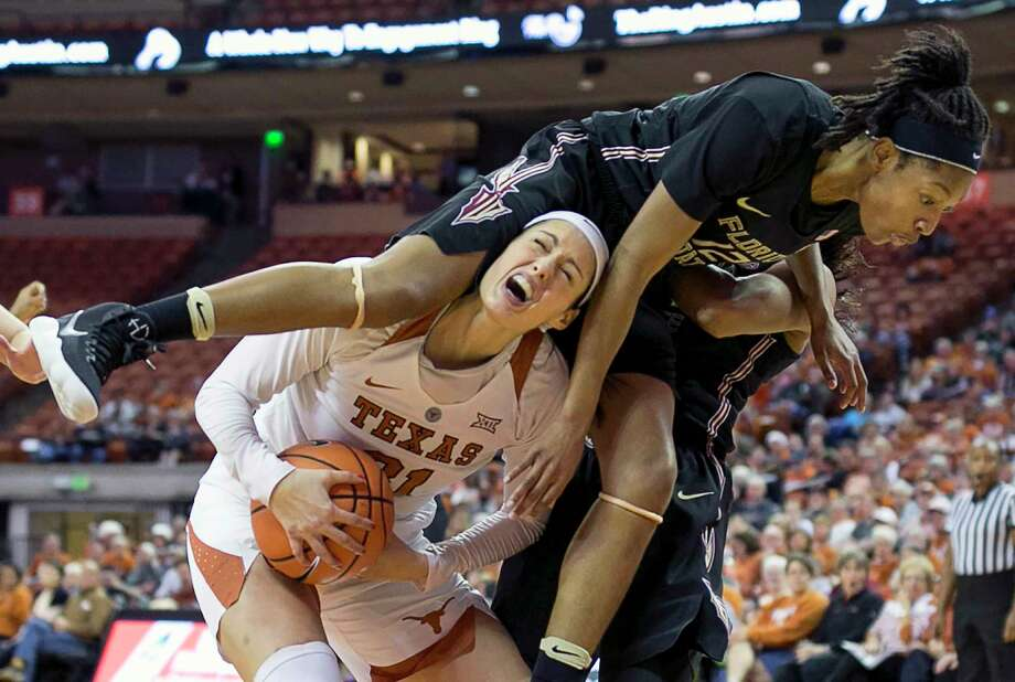 It is all Texas' Audrey-Ann Caron-Goudreau can do to maintain control of the ball when Florida State's Nicki Ekhomu, right, lands on her shoulders during Sunday's game in Austin. The Longhorns won 87-72. Photo: Jay Janner, MBO / Austin American-Statesman