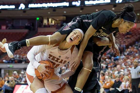 It is all Texas' Audrey-Ann Caron-Goudreau can do to maintain control of the ball when Florida State's Nicki Ekhomu, right, lands on her shoulders during Sunday's game in Austin. The Longhorns won 87-72.