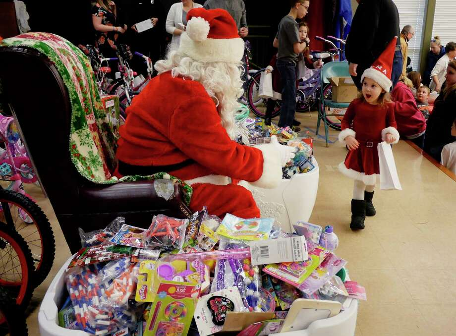 Emma Ralston, 3, of Altamont walks up to meet Santa at the Sheriff's Hometown Christmas party on Sunday, Dec. 17, 2017, in Voorheesville, N.Y.  The Sheriff's Department began helping 29 years ago with one family.  This year the department, through the generosity of the community, helped 190 children have gifts for Christmas.   (Paul Buckowski / Times Union) Photo: PAUL BUCKOWSKI / 20042434A