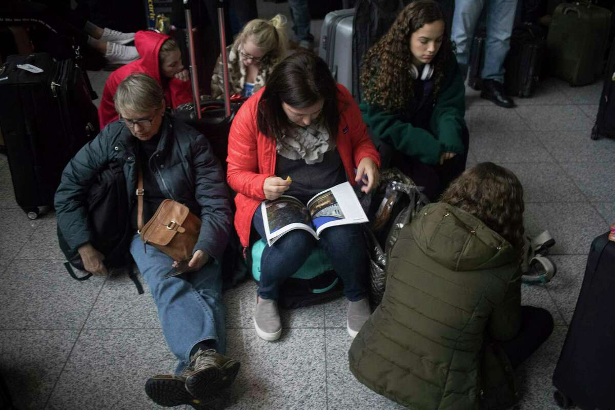 Passengers wait for the lights to come back on at Hartsfield-Jackson International Airport, Sunday, Dec. 17, 2017, in Atlanta. A sudden power outage at the Hartsfield-Jackson Atlanta International Airport on Sunday grounded scores of flights and passengers during one of the busiest travel times of the year. (Steve Schaefer/Atlanta Journal-Constitution via AP) ORG XMIT: GAATJ305