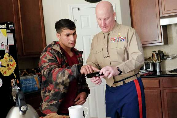 "Mohammed ""Jay"" Younus Yousafzoy, 24, goes over photos with Lt. Col. Mike Hudson on Nov. 29, 2017, in Houston. ( Elizabeth Conley / Houston Chronicle )"