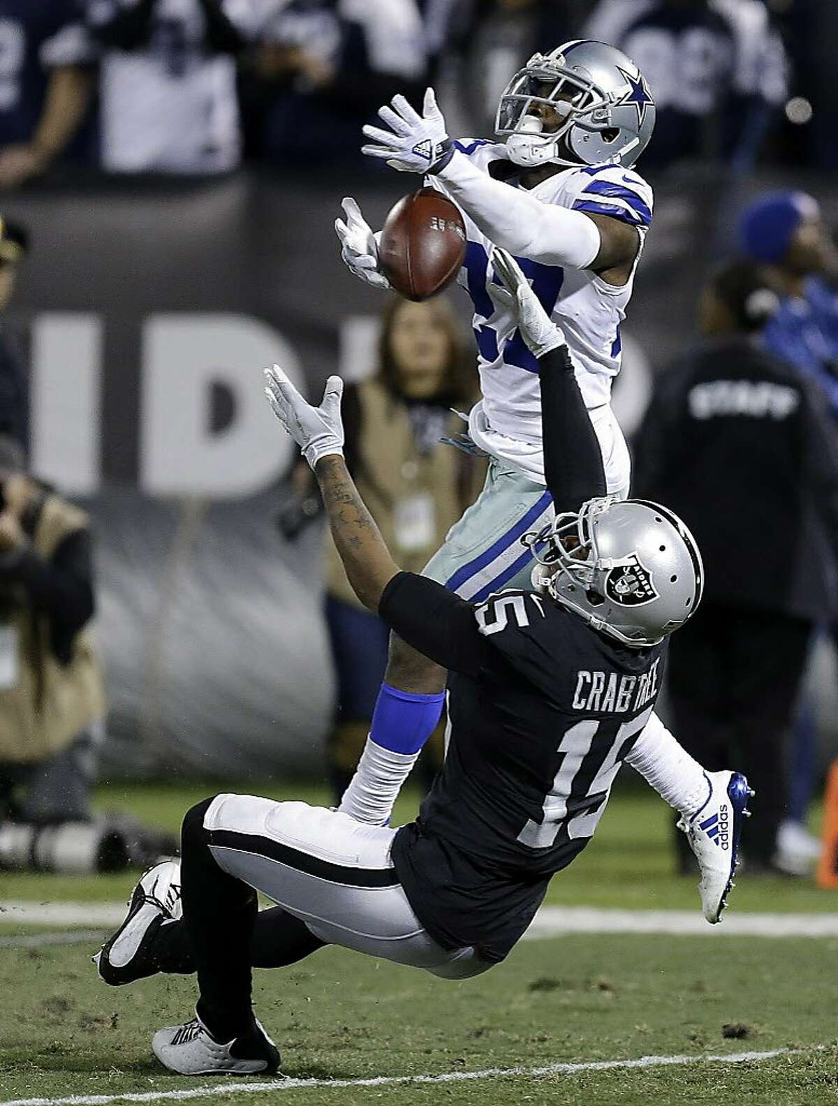 Dallas Cowboys cornerback Jourdan Lewis (27) is called for an interference penalty while defending a pass intended for Oakland Raiders wide receiver Michael Crabtree (15) during the second half of an NFL football game in Oakland, Calif., Sunday, Dec. 17, 2017. The Cowboys won 20-17. (AP Photo/Ben Margot)