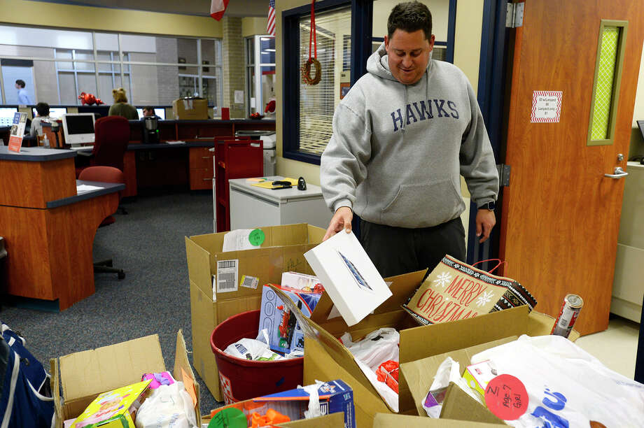 Football coach Jared Sloan looks at items donated by the team in the library at Hardin-Jefferson High School on Thursday. The school's students, including clubs and sports teams, helped collect gifts for needy students at Sour Lake Elementary.  Photo taken Thursday 12/14/17 Ryan Pelham/The Enterprise Photo: Ryan Pelham / ©2017 The Beaumont Enterprise/Ryan Pelham