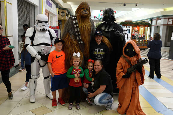 Jan Broussard and grandchildren Landon, Conlin, Paris and Bexley Broussard pose with Star Wars characters at Central Mall on Saturday. The group Charitable Force began two years ago doing appearances at community and charity events free of charge.  Photo taken Saturday 12/16/17 Ryan Pelham/The Enterprise