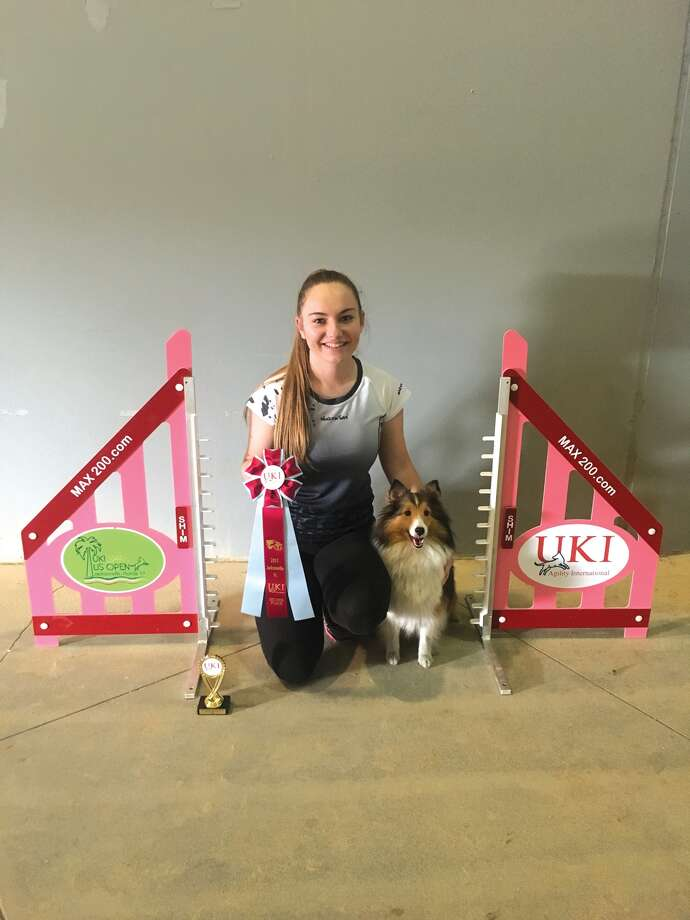 Lydia Carnes and her Sheltie Bella with one of the awards they have won. Photo: For The Intelligencer