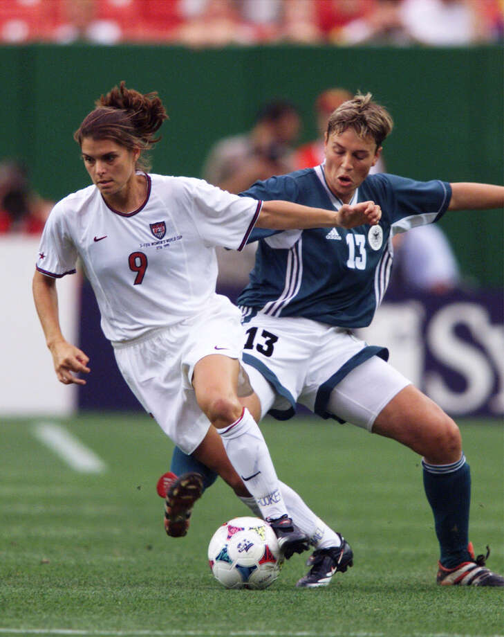 SPORTS / ADVANCE -- LOCAL OLYMPIANS -- The United States' (9) Mia Hamm dribbles past Germany's (13) Sandra Minnert during the first half of a Women's World Cup quarterfinals match at Jack Kent Cooke Stadium, Friday, July 1, 1999, in Landover, Md. Photo: KHUE BUI, AP / AP