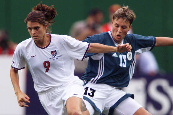SPORTS / ADVANCE -- LOCAL OLYMPIANS -- The United States' (9) Mia Hamm dribbles past Germany's (13) Sandra Minnert during the first half of a Women's World Cup quarterfinals match at Jack Kent Cooke Stadium, Friday, July 1, 1999, in Landover, Md.