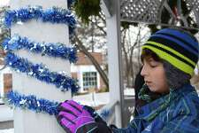 Avery Sterling, 10, of Trumbull, helps with decorations at the Hanukkah menorah lighting on Sherman Green, organized by Chabad of Fairfield, Sunday, Dec. 17, 2017, in Fairfield, Conn.