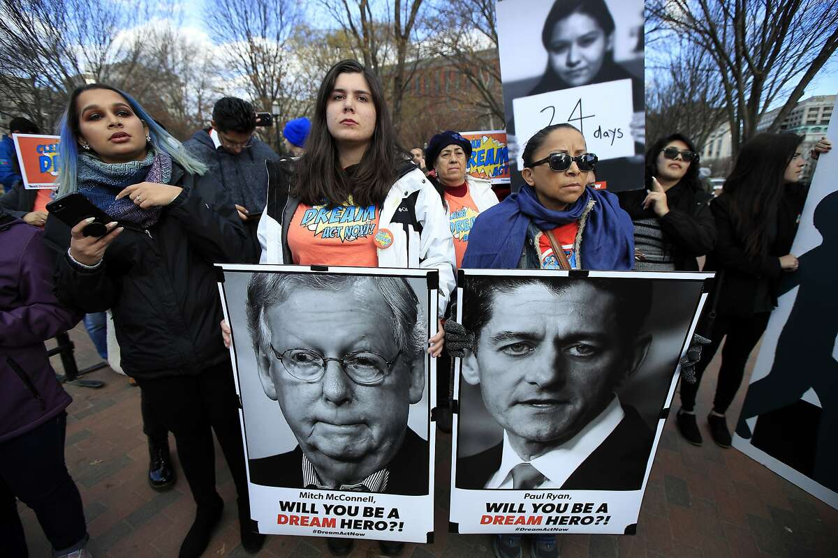 Amanda Bayer, left holding banner, and Marisol Maqueda, right with banner, from Mexico whose daughter Maria Torres also from Mexico City is a DACA recipient finishing her masters degree in Arizona, join a rally outside the White House in Washington, Thursday, Dec. 7, 2017. (AP Photo/Manuel Balce Ceneta).