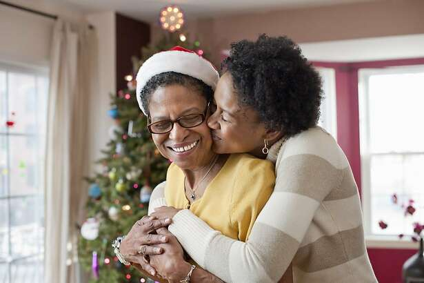 senior woman wearing Santa hat standing in front of Christmas tree with her adult daughter