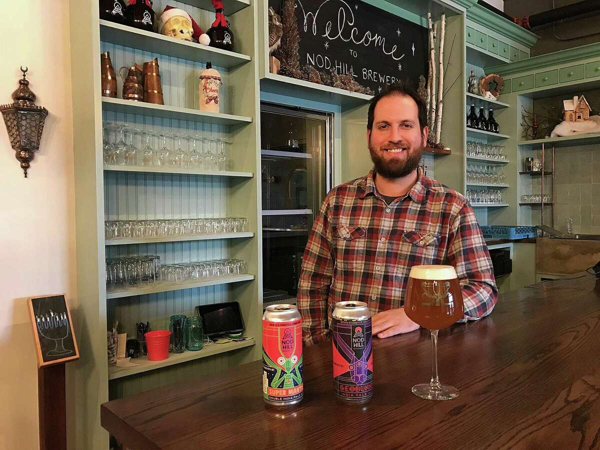 David Kaye of Nod Hill Brewery stands behind cans of Geobunny IPA and Super Mantis Double IPA, the brewery's first can releases, in Ridgefield, Conn., on Monday, Dec. 18, 2017.