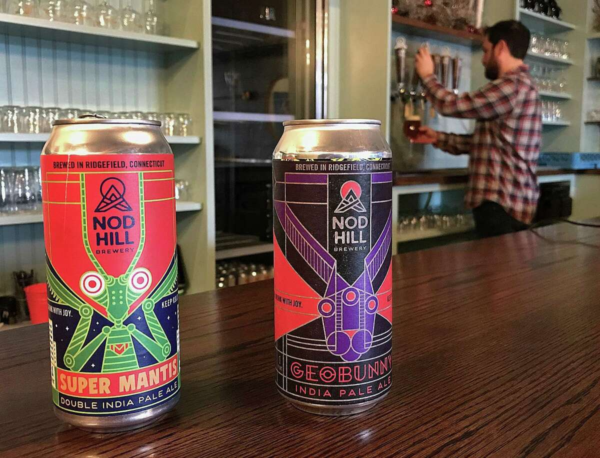 David Kaye of Nod Hill Brewery pours a beer from a tap as cans of Geobunny IPA and Super Mantis Double IPA, the brewery's first can releases, sit on the bar at the brewery in Ridgefield, Conn., on Monday, Dec. 18, 2017.