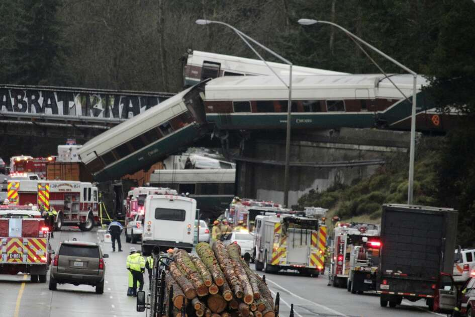 "A derailed train is seen on southbound Interstate 5 on Monday, Dec. 18, 2017, in DuPont, Wash. An Amtrak train making an inaugural run on a new route derailed south of Seattle on Monday, spilling train cars onto a busy interstate in an accident that resulted in ""multiple fatalities"" and numerous injuries, authorities said."
