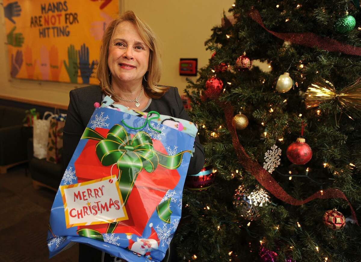 President/CEO Debra Greenwood holds one of many gifts donated to benefit clients at The Center for Family Justice in Bridgeport. Greenwood said domestic violence incidents tend to decrease during the holidays, but pick up strongly again in the new year. The center is the primary domestic violence shelter in the region.