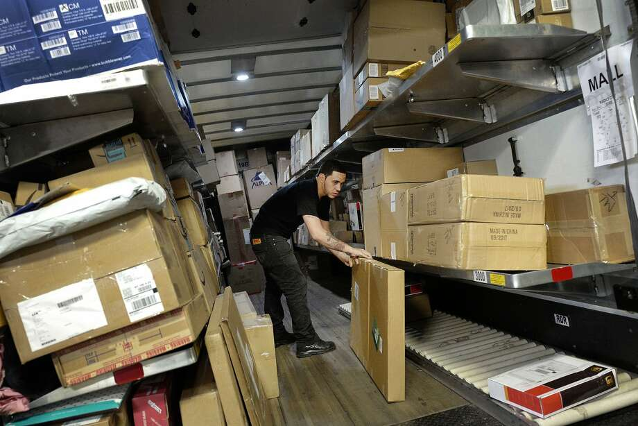 Packages get sorted for delivery.  Photo: Mark Lennihan, Associated Press