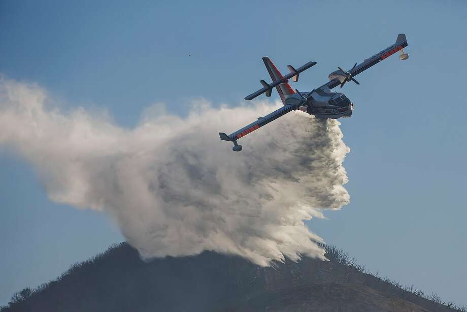 An aircraft drops water on a hot spot Sunday in the hills near Montecito (Santa Barbara County). More than 8,000 firefighters from nearly a dozen states are battling the huge blaze. Photo: Marcus Yam, TNS