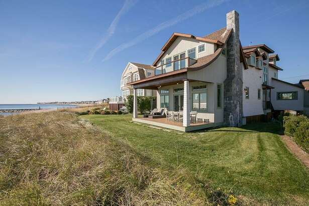 The custom colonial house at 825 Fairfield Beach Road has a covered deck that enjoys panoramic views of Long Island Sound.