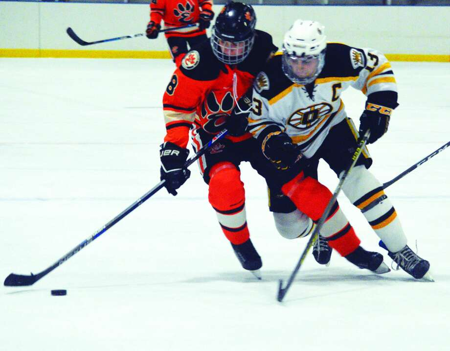 Edwardsville's Collin Salter, left, tries to keep the puck away from an Oakville player during a regular-season game.