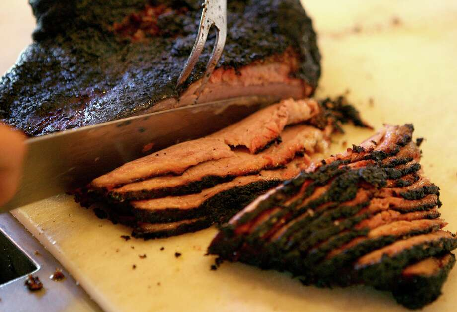 Slices of brisket come off the cutting line. Photo: Express-News File Photo / San Antonio Express-News