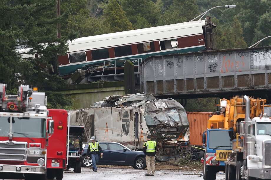 """A derailed train is seen on southbound Interstate 5 on Monday, Dec. 18, 2017, in DuPont, Wash. An Amtrak train making an inaugural run on a new route derailed south of Seattle on Monday, spilling train cars onto a busy interstate in an accident that resulted in """"multiple fatalities"""" and numerous injuries, authorities said. Photo: GRANT HINDSLEY/SEATTLEPI"""