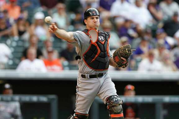 FILE - In this June 7, 2015, file photo, Miami Marlins catcher J.T. Realmuto throws to first base to put out Colorado Rockies first baseman Wilin Rosario in the ninth inning of a baseball game, in Denver. The stolen base has been stolen from much of baseball, an afterthought when spring training starts next week. Sabermetrics have played a huge role in the steal's decline. When a hitter steps into a batter's box and a runner takes a lead, managers and coaches know the pitcher's delivery time to home plate and the catcher's pop time _ the second-plus lag between the ball hitting the mitt and it touching the middle infielder's glove.