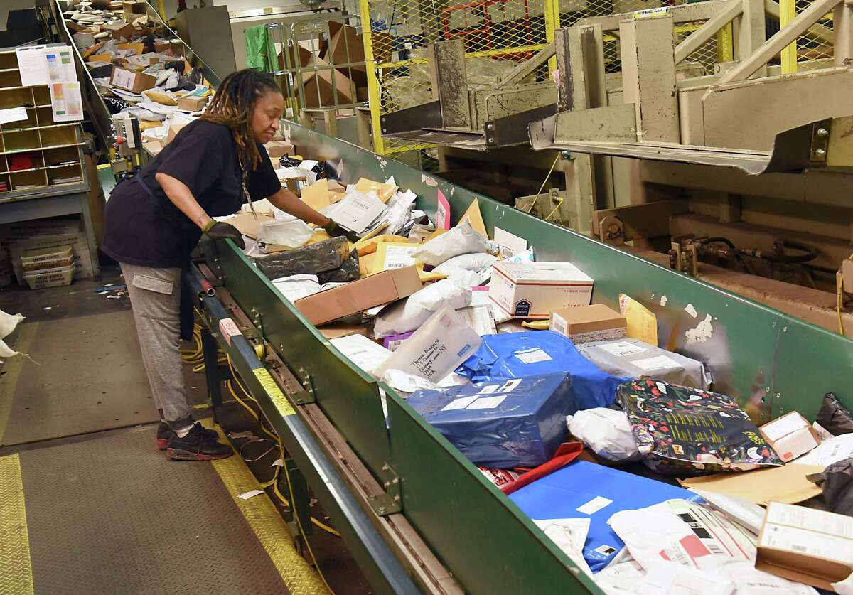 Postal employee Kimberly Mosley pushes parcels down a conveyor belt in the Albany Processing and Distribution Center on the USPS's busiest day of the year on Monday, Dec. 18, 2017 in Albany, N.Y. (Lori Van Buren / Times Union)