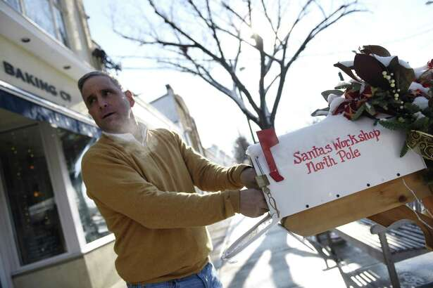 York Construction & Development owner Nick Barile opens letters to Santa from the North Pole mailbox outside his business in Old Greenwich, Conn. Thursday, Dec. 14, 2017. For four years, Nick and his wife, Jill, have collected children's letters to Santa from a mailbox outside their business and have sent letters back with holiday wishes and candy.