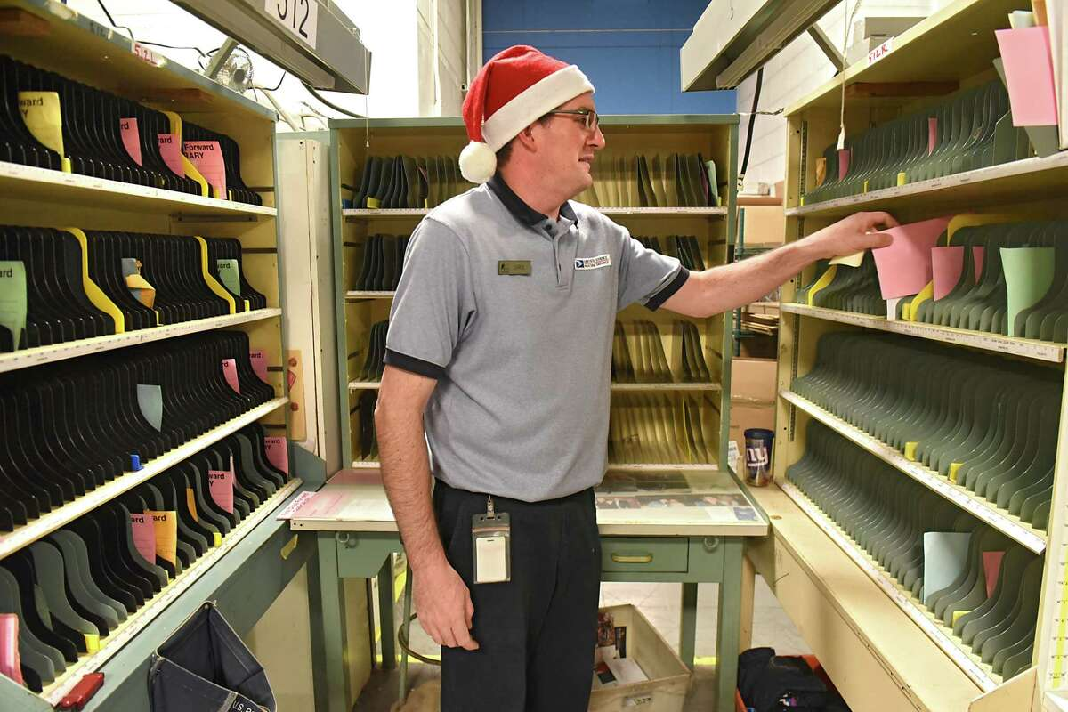 Window clerk Chris Cornish works in an area where postal carriers sort their mail at the Albany Processing and Distribution Center on the USPS's busiest day of the year on Monday, Dec. 18, 2017 in Albany, N.Y. (Lori Van Buren / Times Union)