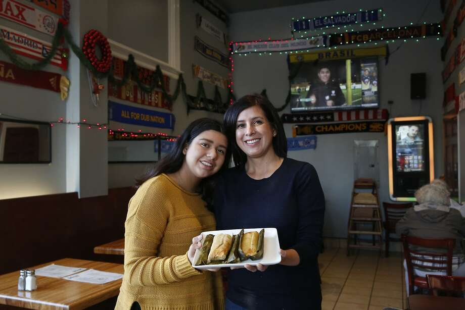 Jackie Vela (right) and her daughter Andrea Gil hold a plate of chicken tamales from a Salvadoran recipe at Balompie Cafe #3 in S.F. Photo: Lea Suzuki, The Chronicle
