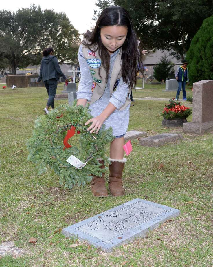 Katelyn Nitsche of Girl Scout Troop 17384 lays a wreath on Veteran's graves during the Wreaths Across America Ceremony at the Magnolia Cemetery in Katy, TX on Saturday, December 16, 2017. Photo: Craig Moseley, Staff / ©2017 Houston Chronicle