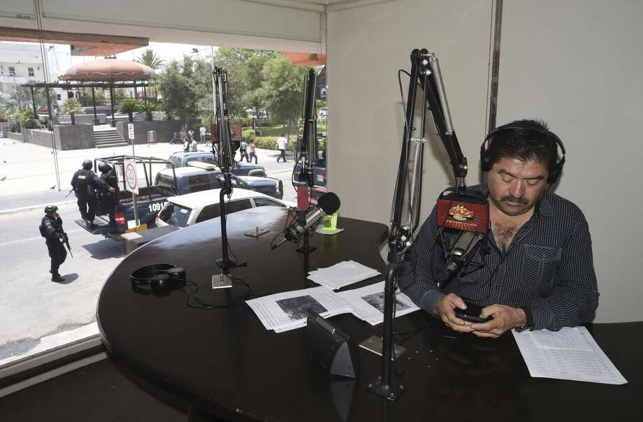 """Reynosa radio broadcast journalist Francisco """"Paco"""" Rojas works his afternoon show as federal police patrol the plaza on Friday, May 12, 2017. Photo: Billy Calzada/San Antonio Express-News"""