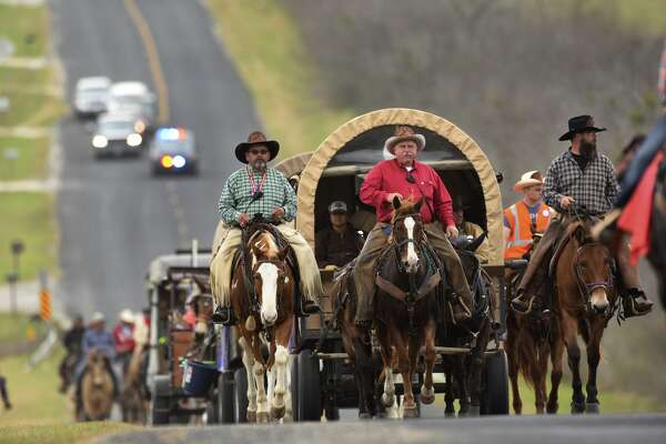 Trail boss Arlis Young, middle, leads the South Texas Trail Riders along Hildebrandt Road on their way into San Antonio for the Stock Show & Rodeo on Friday, Feb. 10, 2017. The group traveled almost 150 miles.