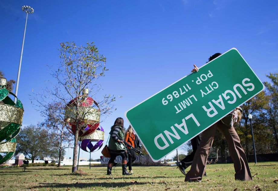 Paulina Valero, who works in the office of strategic initiatives at the City of Sugar Land, carries one of the new population signs that the city will begin erecting Tuesday after annexing Greatwood and New Territory Monday, Dec. 11, 2017, in Sugar Land.  ( Mark Mulligan / Houston Chronicle ) Photo: Mark Mulligan, Houston Chronicle / © 2017 Houston Chronicle