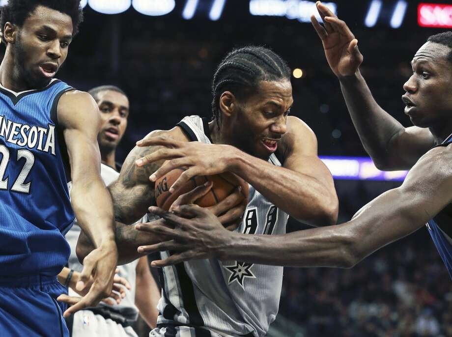 Kawhi Leonard rips away a defensive rebound from Andrew Wiggins (left) and Gorgui Dieng in the seccond half as Spurs host the Timberwolves at the AT&T Center on March 4, 2017. Photo: Tom Reel/San Antonio Express-News