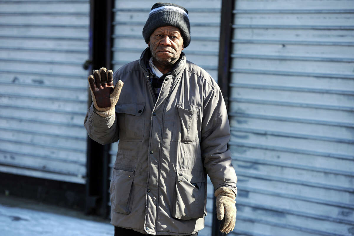 Julian Braxton watches quietly as the annual Martin Luther King Jr. Day march passes his store in Bridgeport, Conn. Jan. 16, 2017. Mr. Braxton recently closed Braxton's Men Shop after 47-years in business.