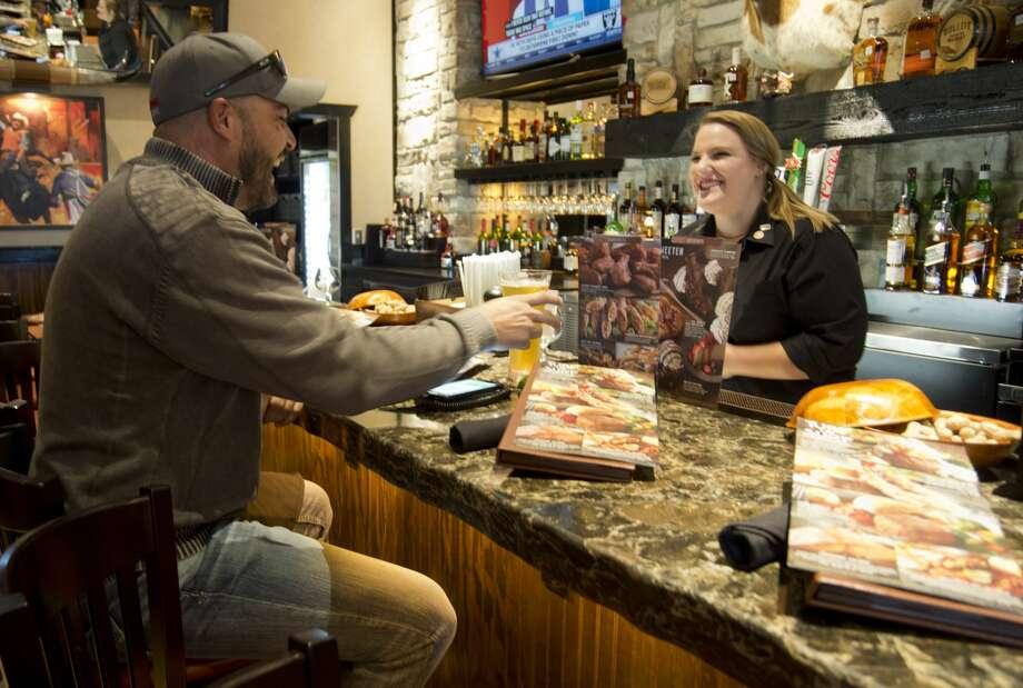 Hoy Boyson enjoys a beer 12/18/17 as he talks with Julie Albers, bartender at Longhorn Steakhouse. Tim Fischer/Reporter-Telegram Photo: Tim Fischer/Midland Reporter-Telegram