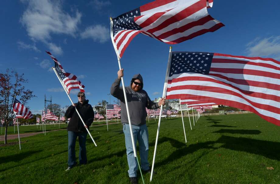 Members of the Norwalk Exchange Club including Dave Witter and his wife Dana Witter plant 200 American flags Friday, November 10, 2017, at Veterans Memorial Park creating a field of honor for the Club's Veterans Day Ceremony Saturday at the park in Norwalk, Conn. The ceremony will follow the city's event at City Hall. Photo: Erik Trautmann/Hearst Connecticut Media