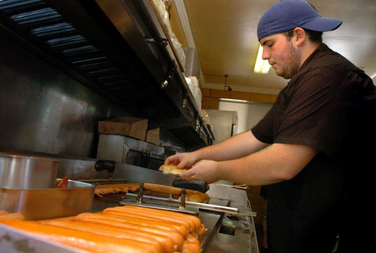 Kyle Hamilton, of Stratford, mans the hot dog grill at Danny's Drive-In, on Ferry Boulevard in Stratford, Tuesday June 29, 2010. The popular fixture has been in business for 75 years.