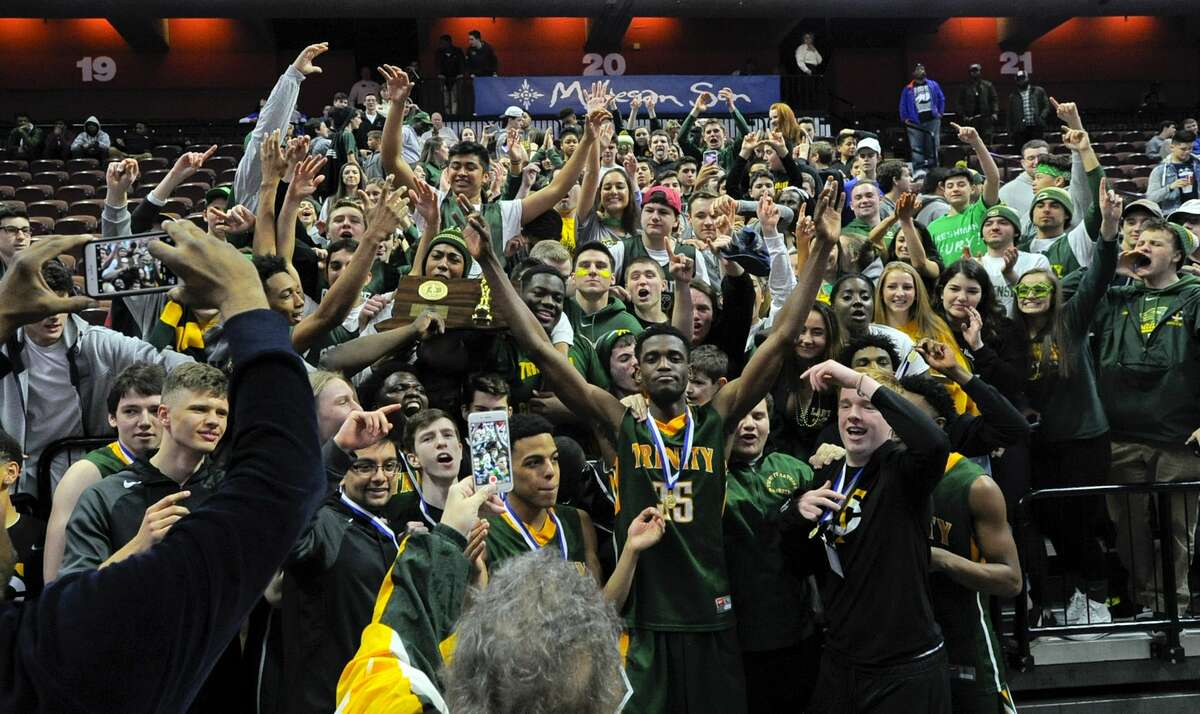 Trinity Catholic Dimitry Moise, center, celebrates with fans following the Crusaders 61-52 win over Woodstock Academy in the CIAC Class S boys basketballl final at The Mohegan Sun Arena in Uncasville, Conn. on March 18, 2017.