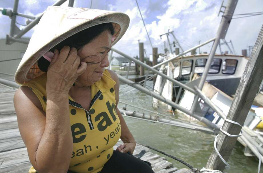 Le An Thi holds back tears while overlooking her family's  shrimping  boat as it rests in the water after sinking at the dock as Rockport  tries to recover from Hurricane Harvey devastation on September 26,  2017.  The family of the owner had just invested $75,000 three days  prior to seeing it destroyed. Photo: Tom Reel/San Antonio Express-News
