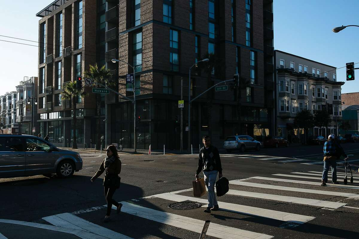 People walk on the cross as the new Bill Sorro Community building is seen in the background on the corner of 6th Street and Howard Street in San Francisco, Calif. Thursday, December 14, 2017.
