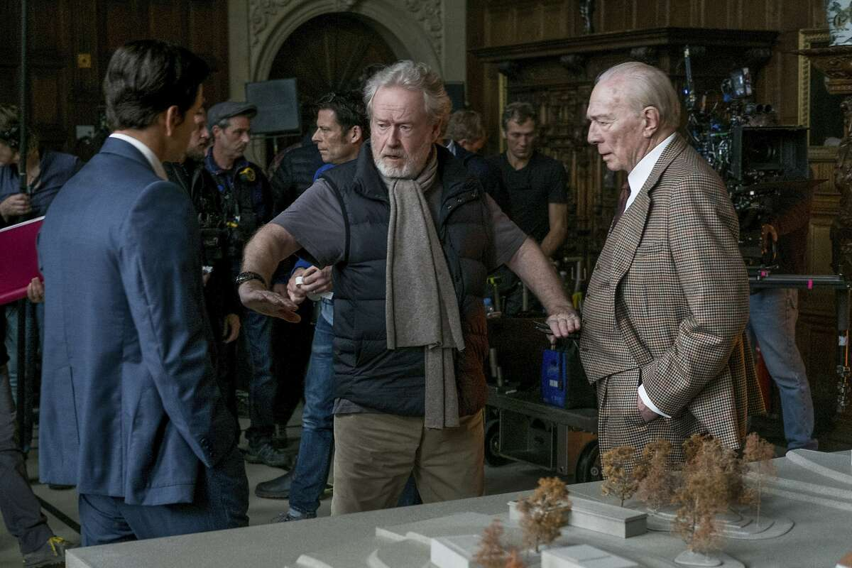 This image released by Sony Pictures shows actors Mark Wahlberg, left, and Christopher Director, right, listening to director Ridley Scott on the set of TriStar Pictures'