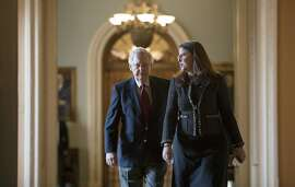 Senate Majority Leader Mitch McConnell, R-Ky., accompanied at right by Secretary for the Majority Laura Dove, walks to his office from the chamber as Republicans in the House and Senate plan to pass the sweeping $1.5 trillion GOP tax bill on party-line votes, at the Capitol in Washington, Monday, Dec. 18, 2017. (AP Photo/J. Scott Applewhite)