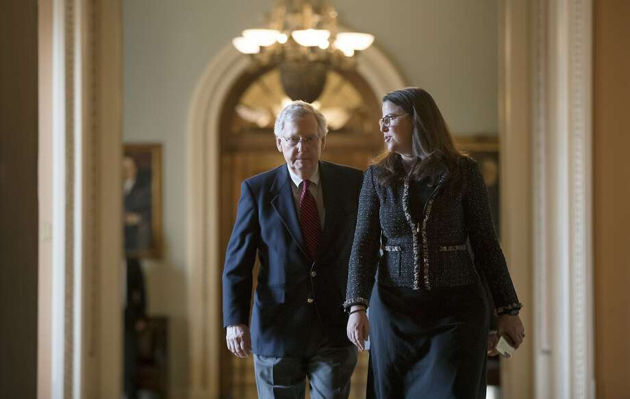 Senate Majority Leader Mitch McConnell and Secretary for the Majority Laura Dove talk on their way to his Capitol office. Photo: J. Scott Applewhite, Associated Press