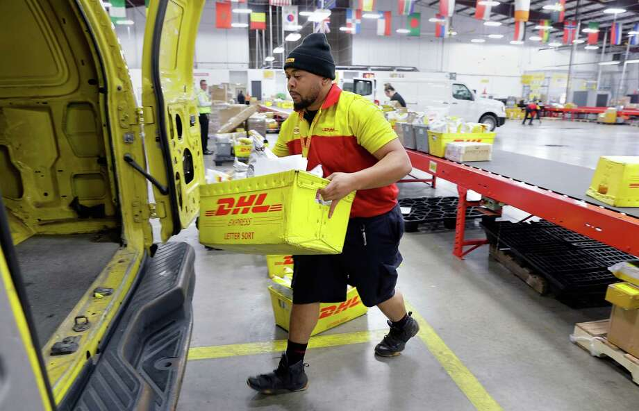 Driver Spencer Clark loads his delivery truck with packages after they have been scanned off of the conveyor line on the busiest shipping day of the year at the DHL facility at the Bush Intercontinental Airport cargo ramp in Houston, TX, Dec. 15, 2017. (Michael Wyke / For the  Chronicle) Photo: Michael Wyke, Freelance / © 2017 Houston Chronicle